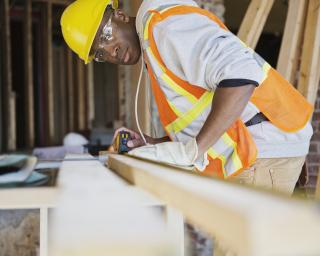 Man measuring a board at a construction site.