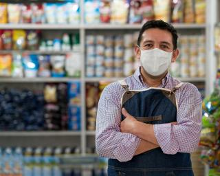 Grocery owner stands in store with arms folded wearing mask.