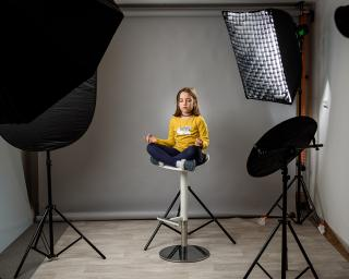 Photographing children in professional photo studio with lighting equipment. Child girl is posing for professional photos with modern flashes in amateur home studio on grey background