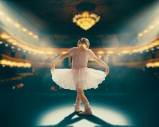 Child girl in a pink tutu dancing on the stage. Little girl is studying ballet.